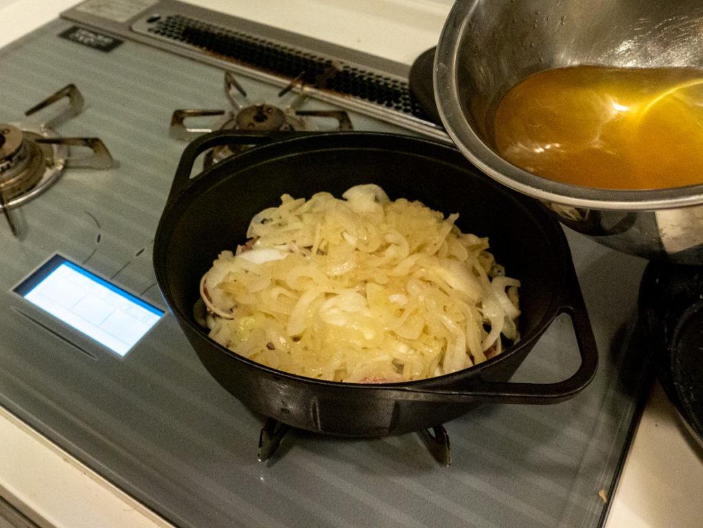 ダッチオーブンにゆで汁を入れるところ
