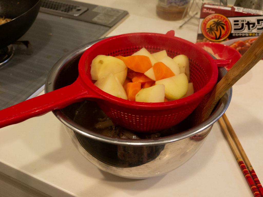 ザルにゆで汁をあけたところ。ザルには茹で上がったジャガイモとニンジン