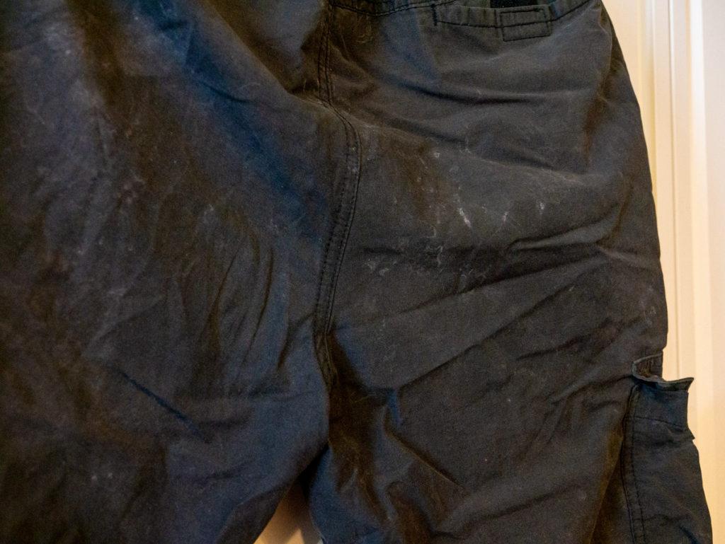 白い汚れがついた黒いズボン